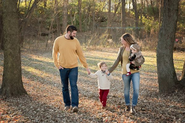 family walking through fall leaves holding hands