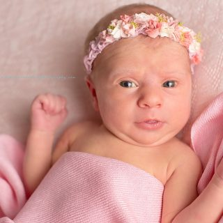 Cute baby girl wearing pink flowered headband with pink wrap on soft pink background