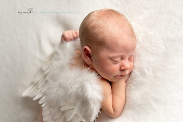 Sweet baby girl wearing angel wings sleeping on soft white background