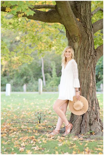 Beautiful high school graduate in white lacy dress leaning against large tree in hazy golden light