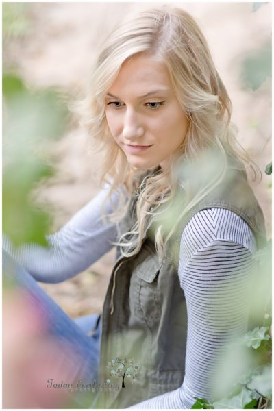 Sweet young lady with soft blonde curls and a gentle smile seen through soft green foliage.