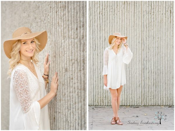 Gorgeous blonde high school graduate in white lacy dress with floppy hat against textured stone background