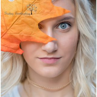 Bold artistic image with vivid colored leaf in the foreground partially covering young ladie's bright blue eyes.