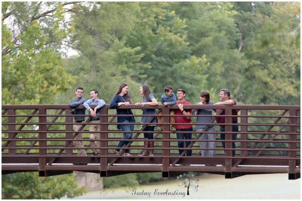 family group laughing together on an old metal bridge